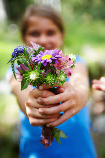 Blurred image of a small girl offering a bunch of flowers
