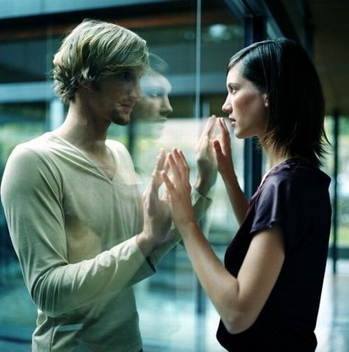 Young couple touching hands through glass, close-up